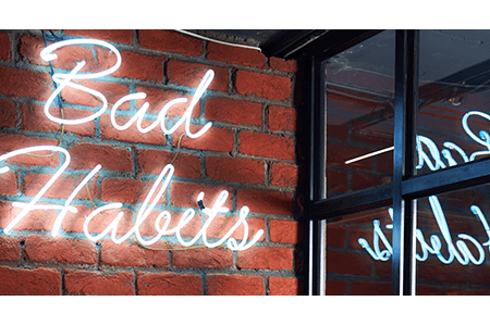 Bad-habits-light-image-on-brick-wall