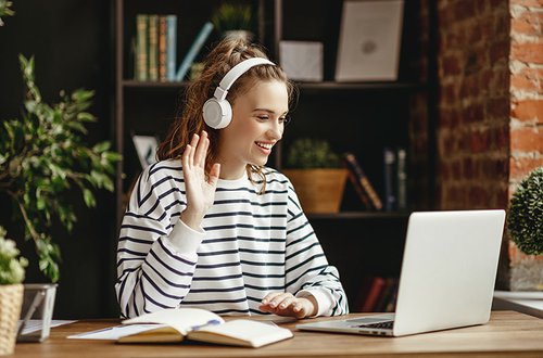 Cheerful-woman-in-headphones-greeting-friend-while-talking-on-laptop-at-home