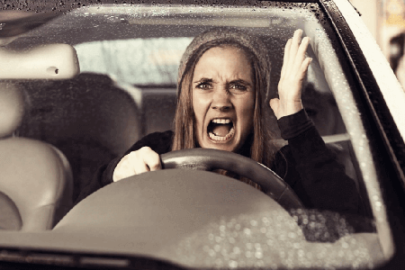 Furious-woman-driving-a-car-in-the-rain-while-cursing-at-other-traffic-participants-article