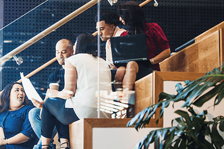 Group-of-colleagues-sitting-on-stairs-talking