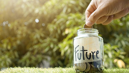 Hand-putting-money-into-jar-labelled-future