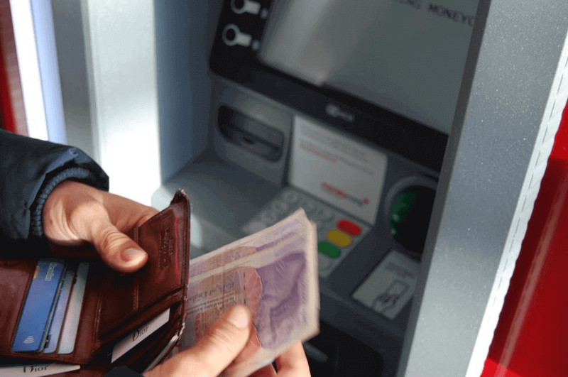 Hand holding wallet with bank notes in it in front of atm
