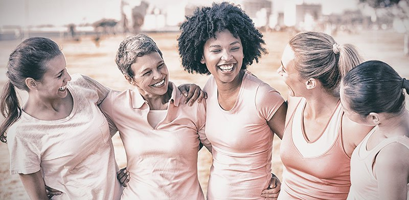 Group of women laughing and wearing pink tshirts for breast cancer awareness
