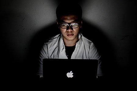 Man sitting in a dark room using his macbook