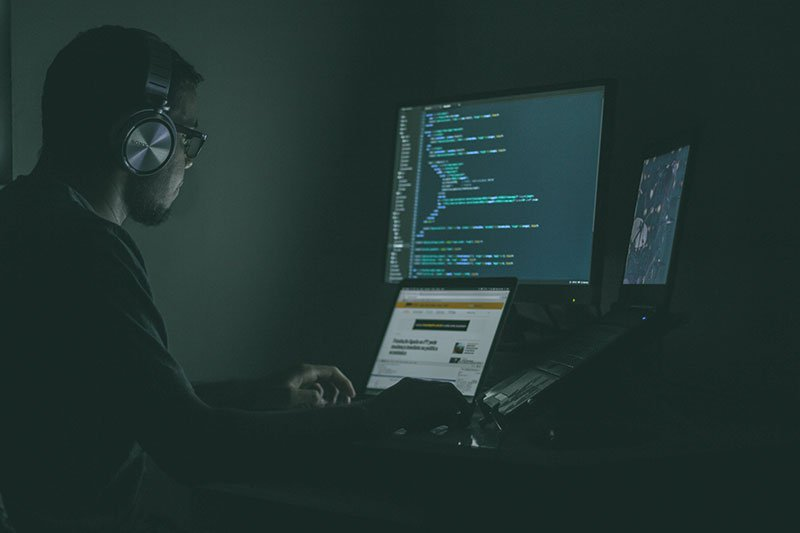 Man in a darkened room using numerous computer screens to hack others