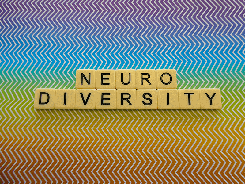 Neurodiversity-spelt-in-scrabble-letters-with-rainbow-zig-zag-background-article