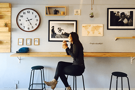 Woman-sitting-on-a-stool-at-a-cafe-enjoying-a-coffee-and-laughing