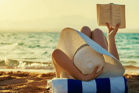 Woman-with-a-giant-sun-hat-reading-a-book-on-the-beach-relaxing-listing-image.png