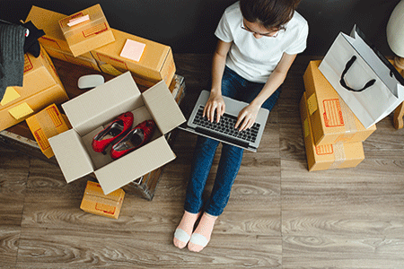 Women-sitting-on-laptop-surrounded-by-opened-and-unopened-boxes-of-online-purchases-listing.gif