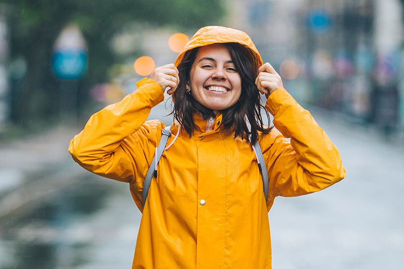 Young smiling woman in raincoat
