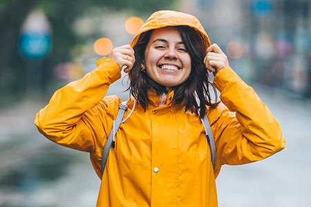Young-smiling-woman-in-raincoat-listing