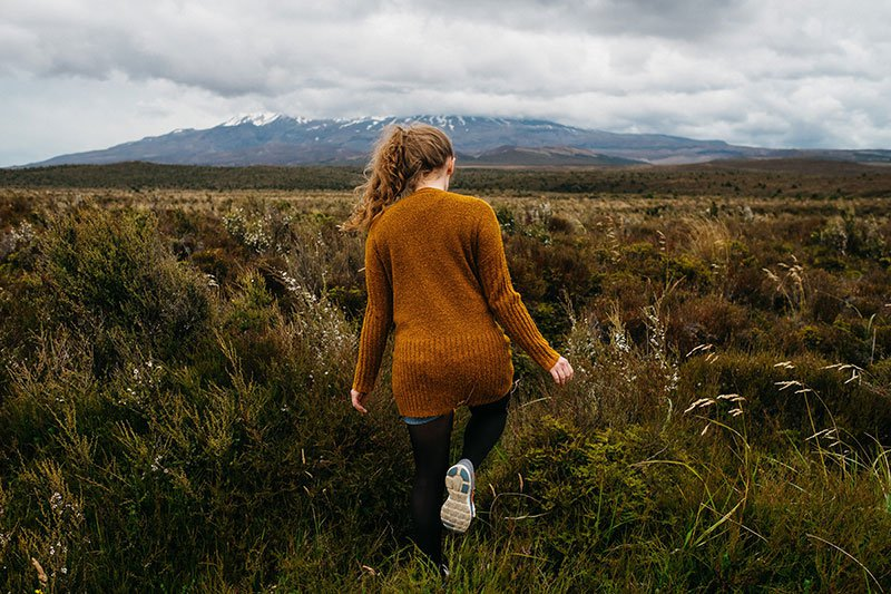 Young woman walking in field with mountain in the background
