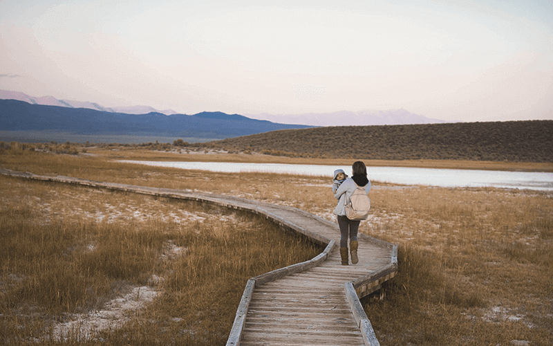 adult-carrying-child-walking-on-path-outside-surrounded-by-hills-and-water