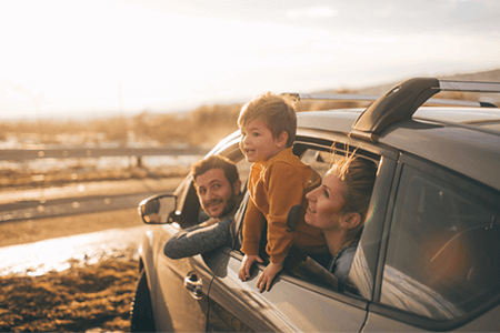 family-in-car-on-the-beach-with-little-kid-hanging-his-head-out-the-window-listing-image.png