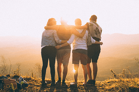 four-young-people-standing-on-hill-top-with-arms-around-each-other-gazing-at-the-sunset-listing-image.png