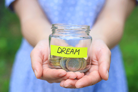 girl-in-blue-dress,-hands-holding-glass-jar-bank-with-dream-note-yellow-sticker-listing.gif