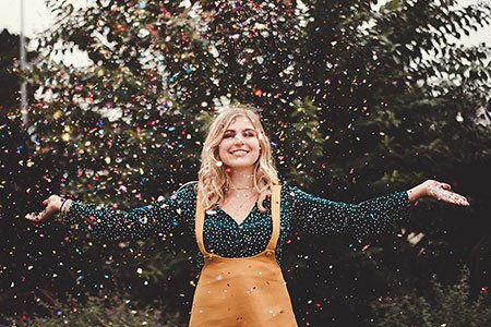 girl-standing-outside-throwing-confetti-in-the-air