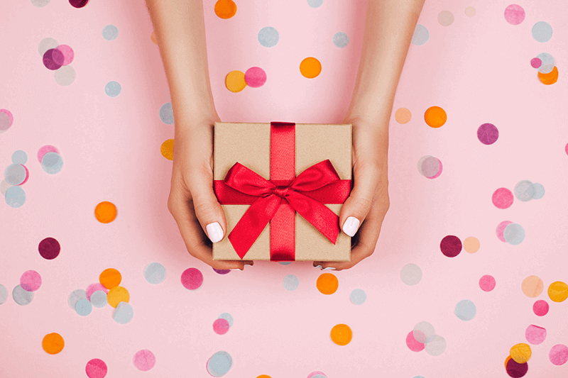 hands-holding-present-with-red-bow
