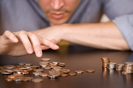 man-counting-coins-in-piles-on-table-listing