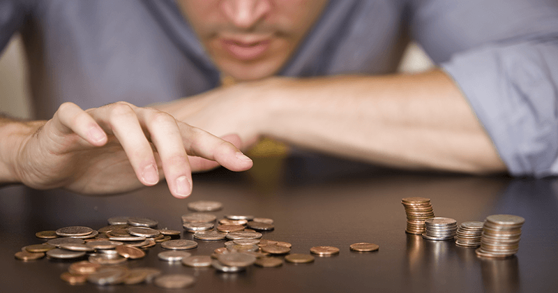 man-counting-coins-in-piles-on-table-article