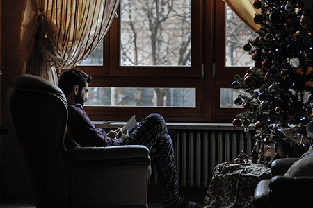 man-sitting-down-in-chair-reading-next-to-a-Christmas-tree-listing-image.png