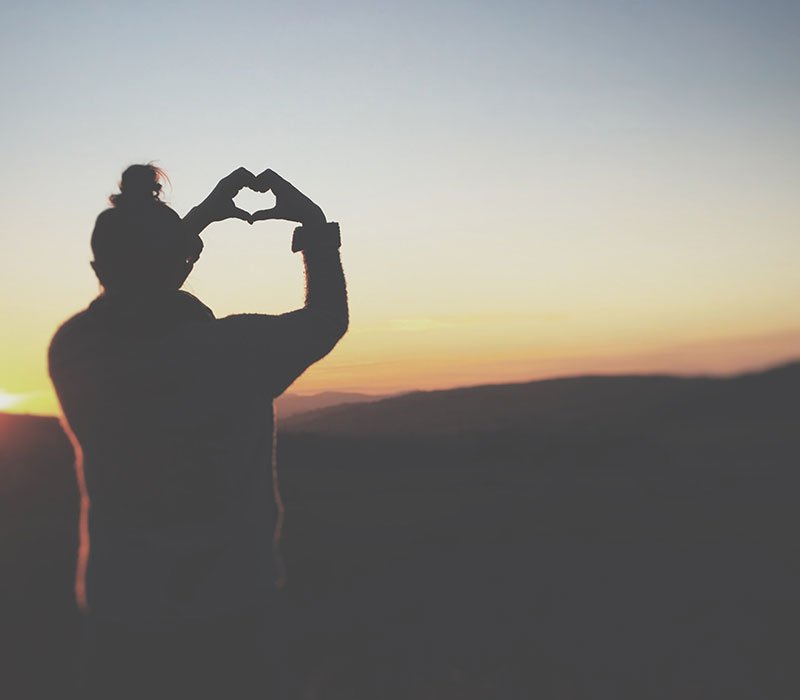 person-standing-on-clifftop-with-fingers-in-heart-shape-watching-the-sunset
