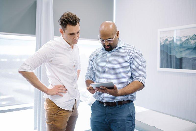two men looking at ipad screen