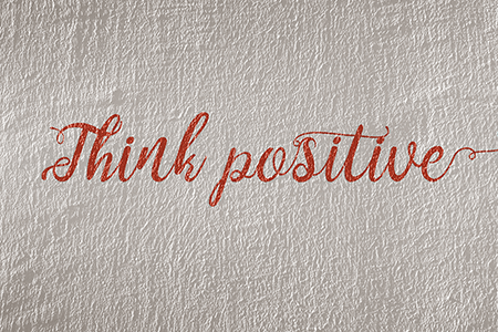 white-concrete-wall-with-text-'think-positive'-written-in-red-cursive-font-article