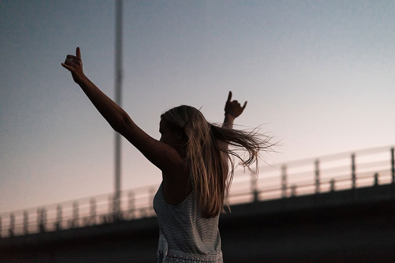 woman raising hands above her