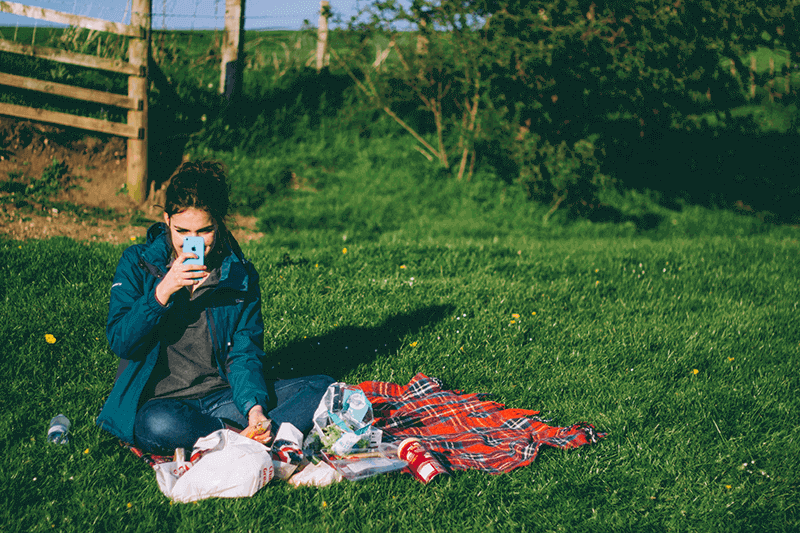 woman-sitting-on-a-picnic-rug-on-the-grass-using-smartphone-for-a-video-call