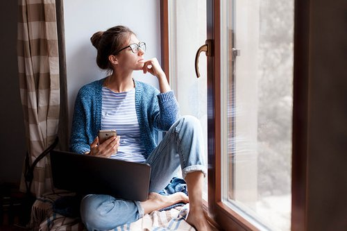 woman-thinking-and-looking-out-window-while-working-on-her-laptop-and-phone