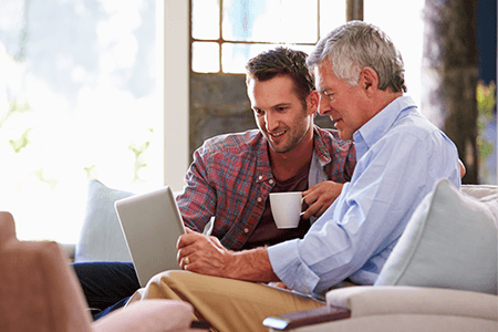 young-man-drinking-coffee-with-older-man-both-looking-at-a-laptop-screen